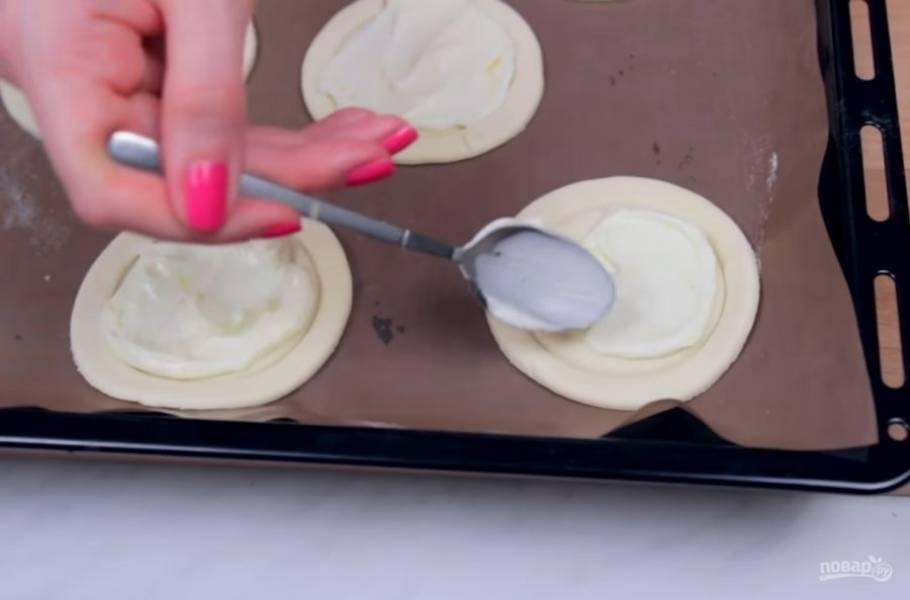 2. Приготовьте крем: сливочный сыр хорошо смешайте с сахаром, цедрой лимона, лимонным соком и ванилином. Нанесите крем с помощью ложки в центр каждого пирожка.