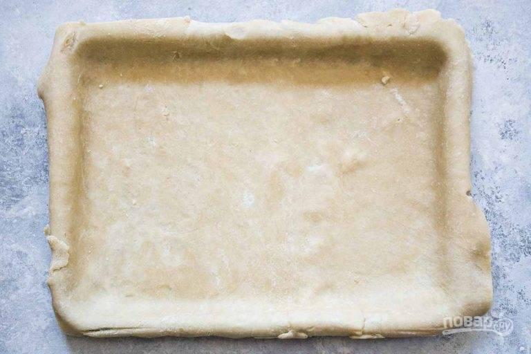 1.Нарежьте холодное масло кусочками, оставьте на 5 минут. Смешайте муку, соль, 1 столовую ложку сахара. Смешайте сливочное масло и мучную смесь, разотрите руками, затем добавьте сметану. Замесите тесто и разделите его на 2 части, каждую оберните в пленку и положите в холодильник на 1 час. Раскатайте одну часть теста в тонкий пласт и выложите в форму для запекания. Отправьте на 15 минут в холодильник.