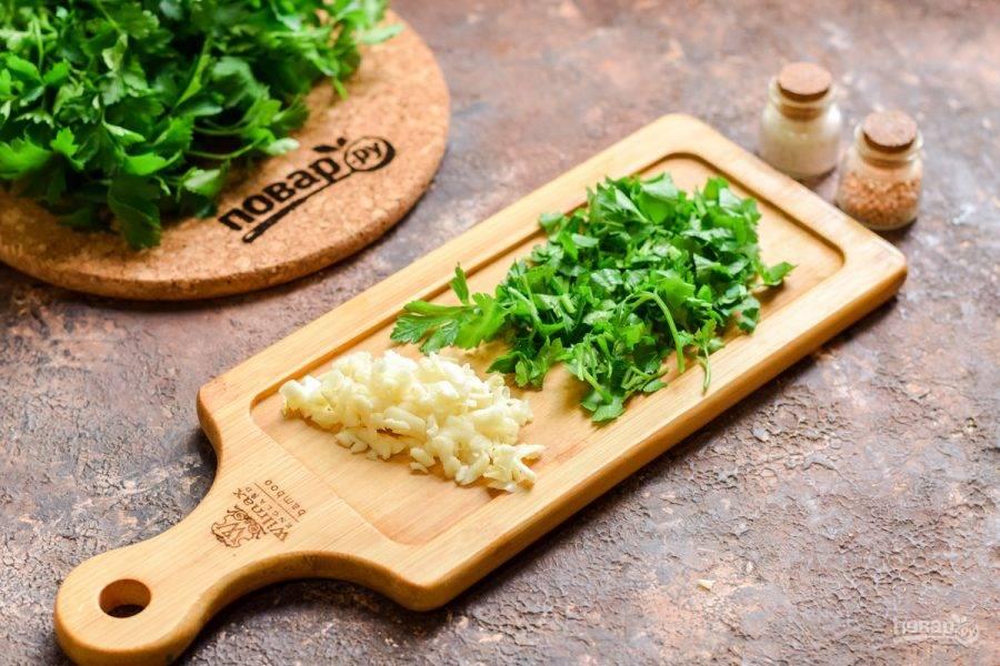 Чеснок очистите, натрите на крупной терке или измельчите ножом. Также нарежьте мелко чистую зелень.