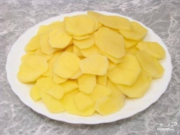 Картофель очистите от кожуры. Промойте его и нарежьте кружками. Морковь почистите, промойте. Нашинкуйте её любым удобным для вас способом.