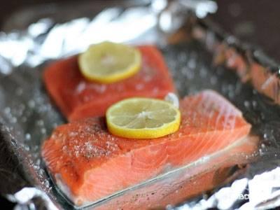 На противень, застеленный фольгой выкладываем стейки, сверху кладем по колечку лимона и закрываем фольгой. Края плотно скрепляем, чтоб не оказалось щелей и из нее не вытек сок лосося. Отправляем запекаться примерно на 15 минут.