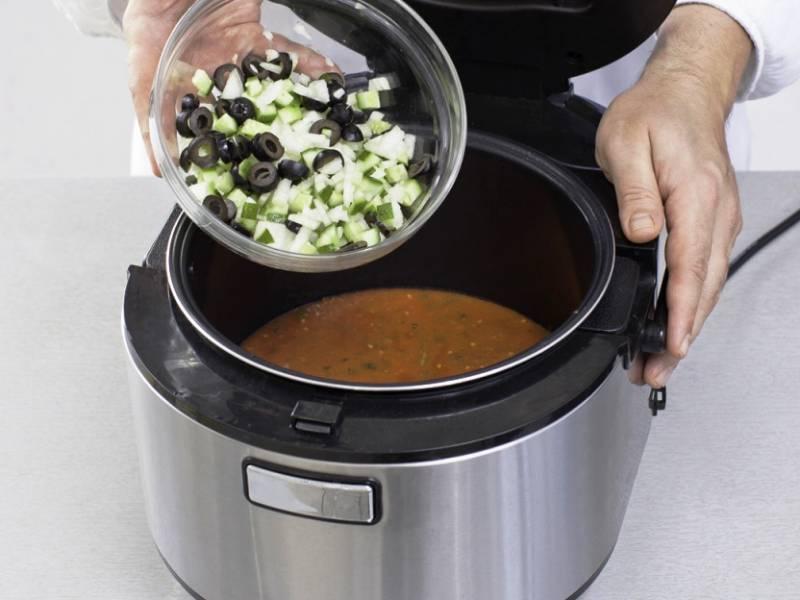Влейте в мультиварку томатное пюре, доведите до кипения, добавьте порезанные овощи и проварите 5 минут. Разлейте по порциям, добавьте в тарелку креветки и подайте с чесночным хлебом.