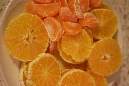 Очистить фрукты. Апельсины нарезать кружочками, мандарины разобрать на дольки.