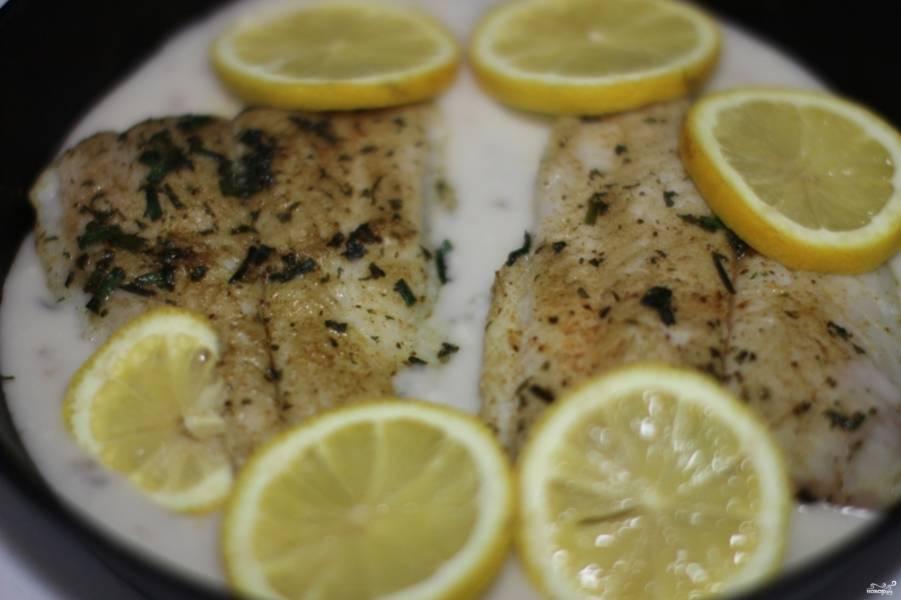 Затем выложите обжаренную рыбу в форму для запекания. Залейте сметаной (необязательно, чтобы всю рыбу накрыло сметаной, можно до половины). Затем выдавите сок лимона равномерно на рыбу, сам лимон можете порезать кольцами и вдавить слегка в сметану (если сметана достаточно жирная, то лимон не утонет).  Отправьте в разогретую духовку на 20 минут.