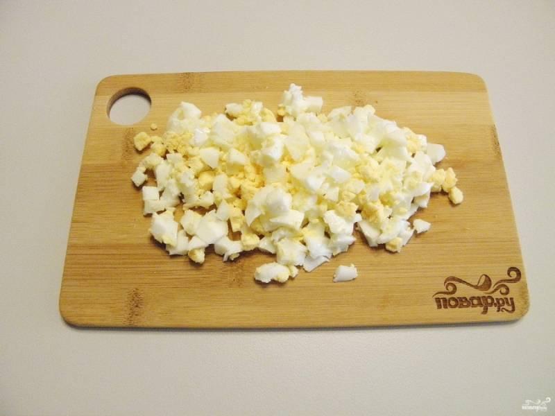 Яйца порубите острым ножом на кубики. Оставьте белок одного яйца и два желтка для украшения варежки.