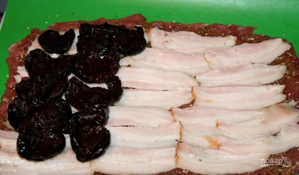 """Отбейте мясо и натрите его солью, перцем и пряностями. Затем нарежьте сало на тонкие пластинки и выложите его на мясо с одной стороны. Чернослив вымойте и разрежьте так, чтобы он """"раскрылся"""". Выложите его на копченое сало."""