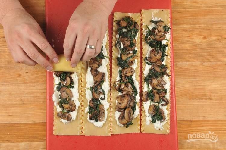 4. Теперь на листы для лазанья разложите сырную смесь, а сверху — грибную со сковороды. Скрутите макаронные листы в рулеты.