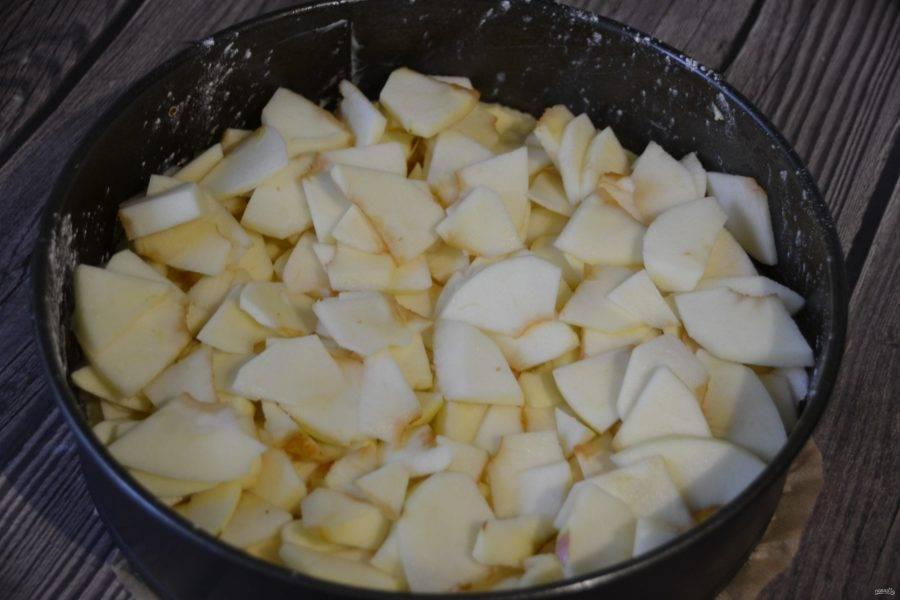 На тесто выложите очищенные и нарезанные на ломтики яблоки.