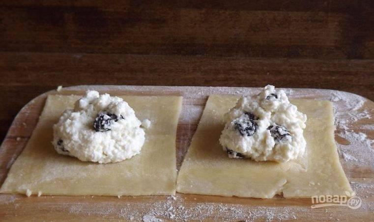 Охлажденное тесто достаньте из холодильника, разверните пищевую пленку и раскатайте его в тонкий пласт. Нарежьте тесто на квадратики и в центр каждого положите по ложке начинки.