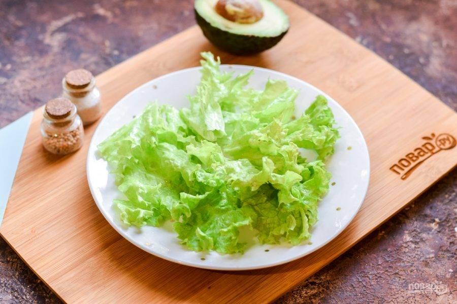Салатные листья сполосните и просушите, порвите руками и выложите на тарелку.