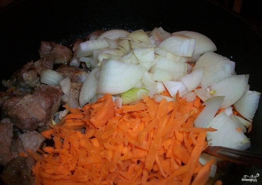 3. Нарезаем лук и морковь и отправляем к мясу. Жарим на слабом огне и также не забываем помешивать.