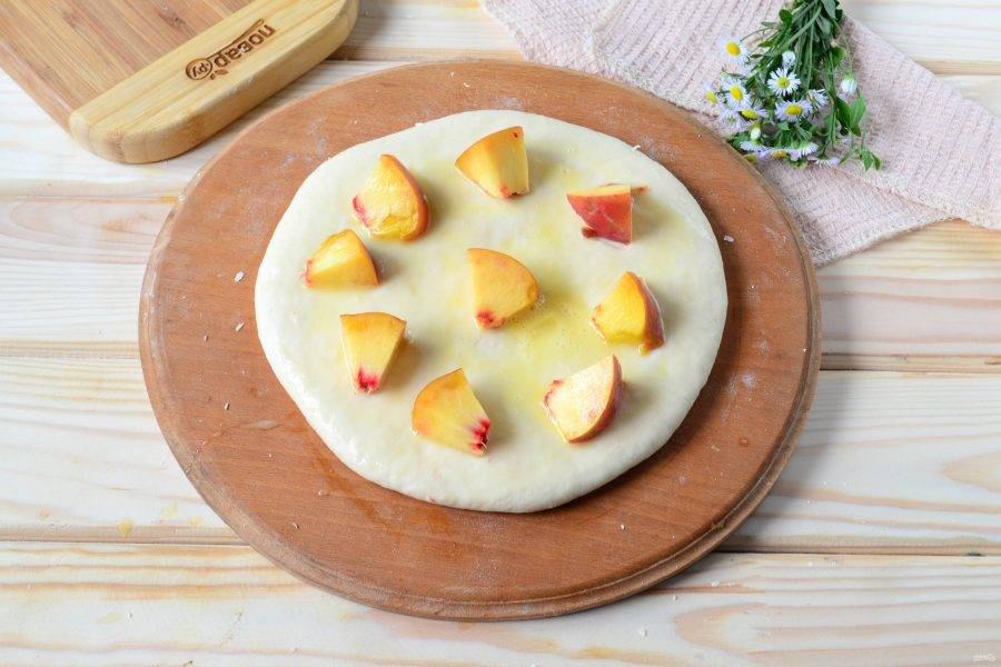 Смажьте верх пирога взбитым яйцом, разложите кусочки персика. Отправьте хачапури с сыром и персиками в духовку на 20-30 минут (температура - 180 градусов).