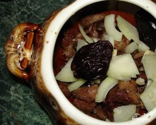 8. Далее используйте горшочки для порционного приготовления. На его дно положите поджаренное мясо, а сверху лук и пару штук чернослива.