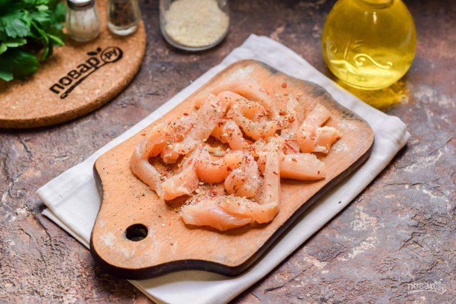 Куриное филе нарежьте небольшими полосками. Посыпьте филе сушеным чесноком, хлопьями перца, солью и молотым перцем.