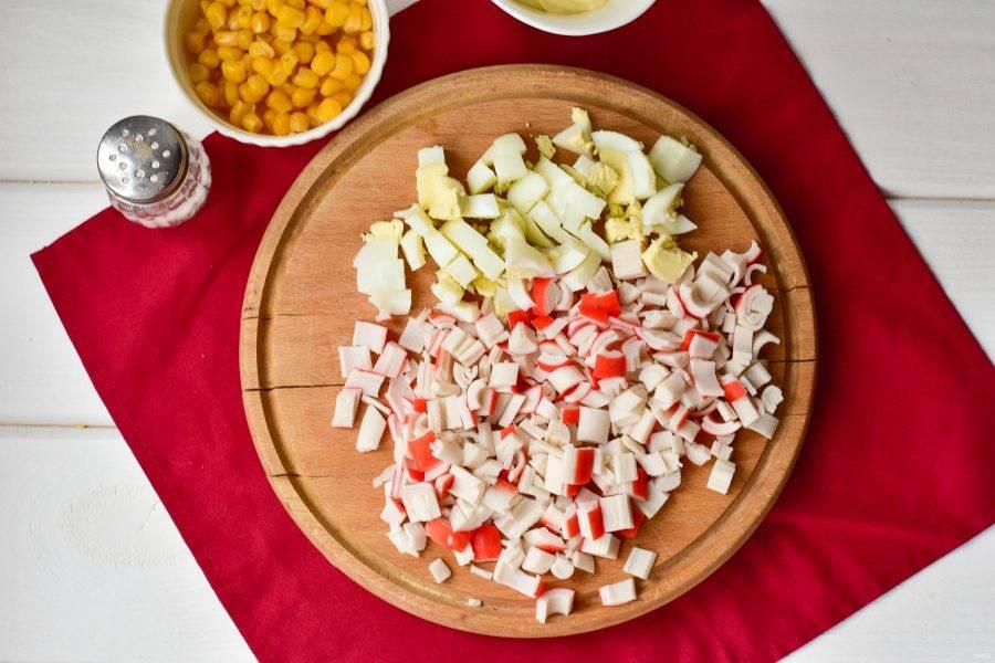 Нарежьте крабовые палочки и вареные куриные яйца кубиками.