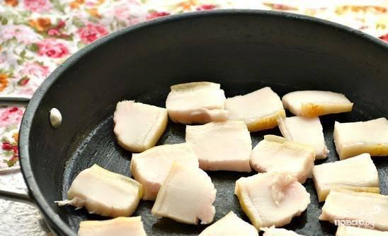 На сковороду выложите кусочки сала. Начните их обжаривать, чтобы выделился жир.