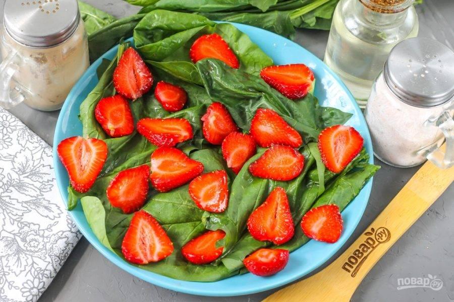 С ягод клубники удалите хвостики, промойте каждую из них в воде и разрежьте пополам, если они мелкие, или нарежьте слайсами, если ягоды крупные. Выложите на промытый шпинат.