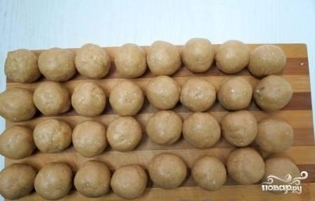 Далее отделяйте от теста небольшие кусочки, из которых затем скатывайте печенья-шарики размером с грецкий орех.