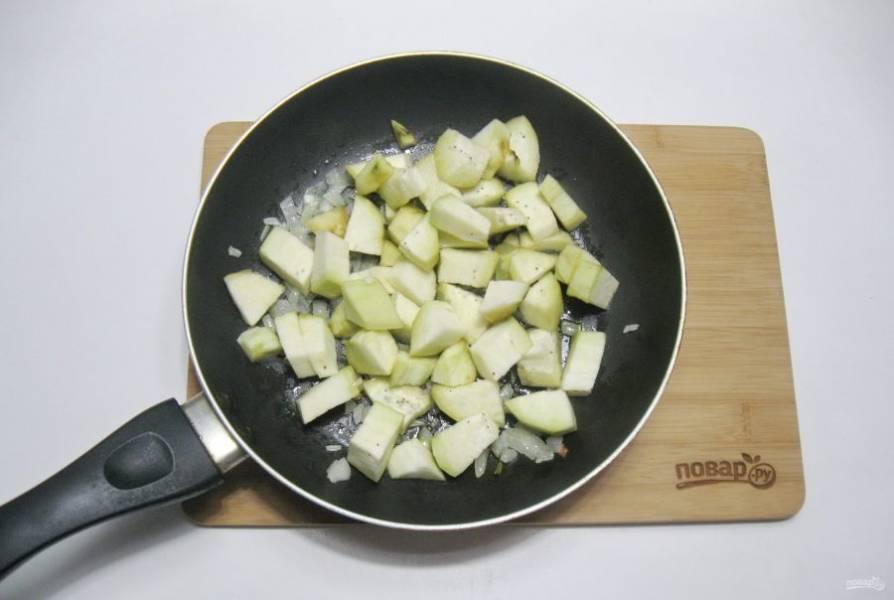 Баклажан помойте, очистите и нарежьте кубиками. Добавьте к луку. Накройте сковороду крышкой и тушите овощи перемешивая 7-8 минут.