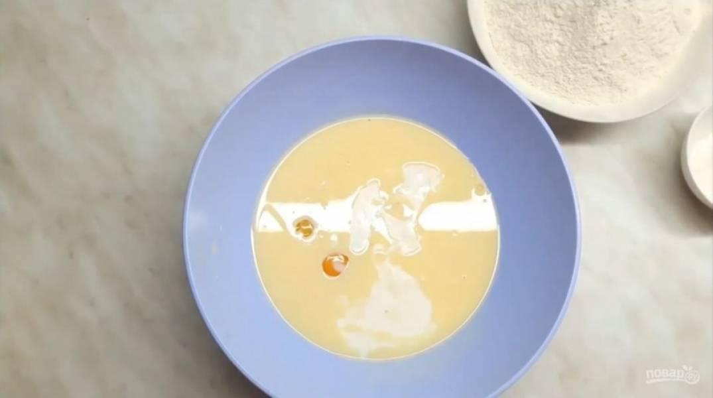 1. Приготовьте жидкую часть теста. Для этого разбейте в миску яйца, добавьте предварительно растопленный маргарин (или сливочное масло), сахар, соль и кефир. Перемешайте все до однородного состояния.