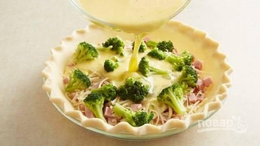 2. Яйца взбейте в глубокой мисочке с молоком. Добавьте соль и перец по вкусу. Вылейте аккуратно на корж и отправьте форму в разогретую до 180 градусов духовку.