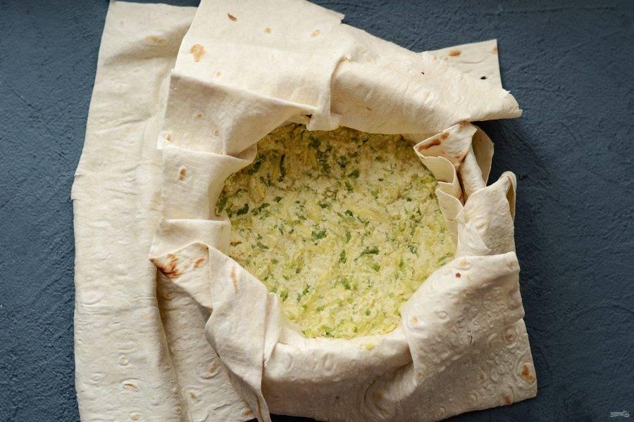 В форму для выпечки выложите один слой лаваша. Смажьте растительным маслом. Выложите ещё один слой лаваша поперёк. В центр переложите начинку.