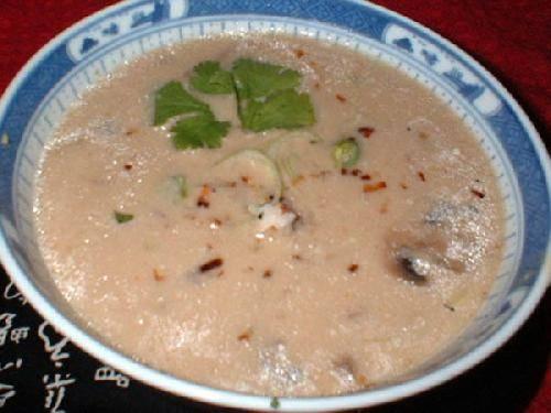 Сожмите лимонный сок в миску. Смешайте с кокосовым молоком. Постепенно сливайте в порей и грибной бульон. Гарнир - кинза и кокосовая стружкай.