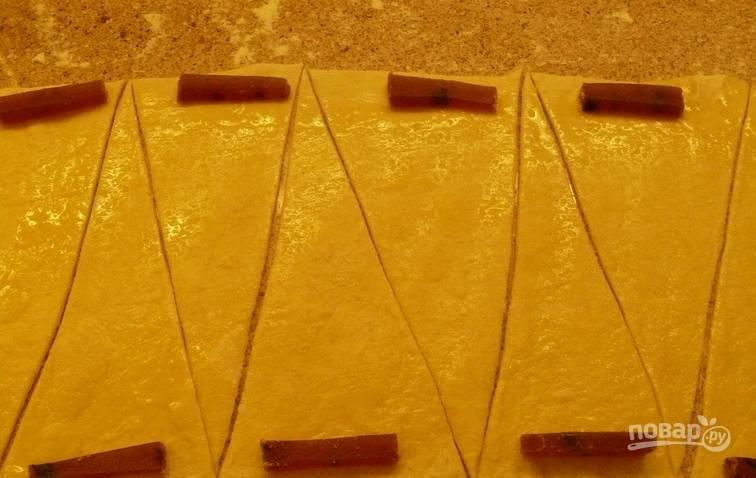 Теперь раскатываем тесто в тонкий пласт на столе, присыпанном мукой. Смазываем его сливочным масло комнатной температуры. Нарезаем тесто на треугольники. На широкую часть каждого треугольника выкладываем кусочек мармелада.