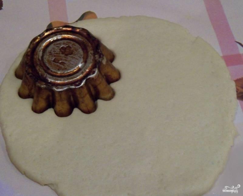 Достаем скалку, посыпаем стол мукой и раскатываем тесто толщиной примерно в сантиметр. Берем металлическую формочку для кексов и выдавливаем из теста фигурки в виде цветочка. Тесто будет оставаться. Из его кусков можно налепить еще печенек.