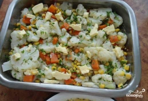 Капусту и морковь порезать на кусочки, выложить на противень, добавить кусочки сливочного масла, залить подготовленной заливкой.