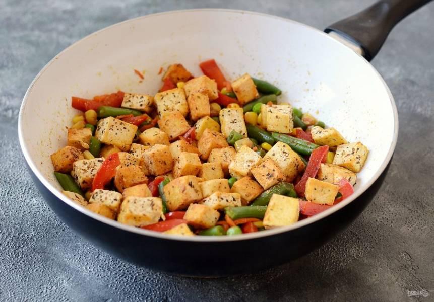 Добавьте к овощами тофу, влейте соевый соус. Перемешайте.
