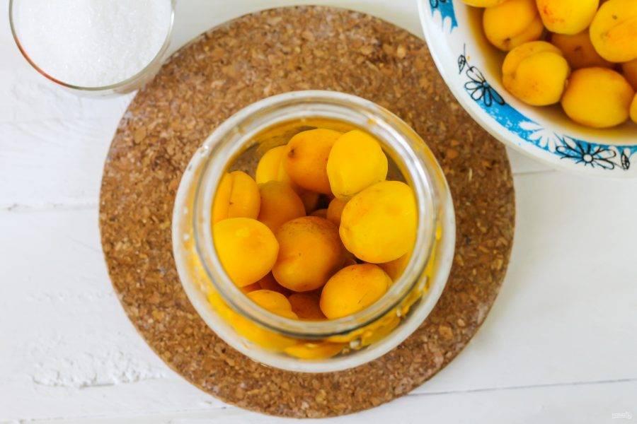 Промойте абрикосы в воде, удаляя подпорченные плоды. Промойте банку с содой и тщательно сполосните. Выложите фрукты в емкость до середины.
