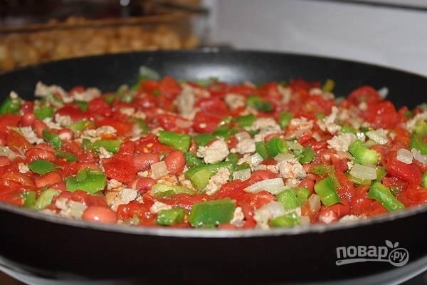 3. Добавьте консервированную фасоль и измельченные помидоры. Перемешайте и томите еще минут 5.