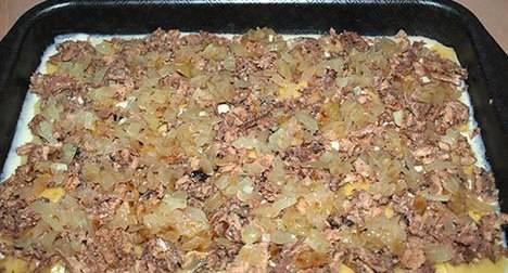 Выкладываем начинку слоями на тесто: вначале будет картофель, его немного посолите (щепотки соли будет достаточно), потом выкладываем сайру, а сверху — лук.
