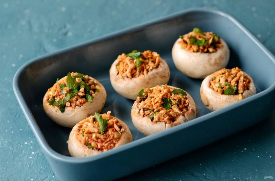 Заполните шляпки шампиньонов начинкой. Выложите грибы в формы для выпечки. Запекайте их 30 минут при температуре 200 градусов.