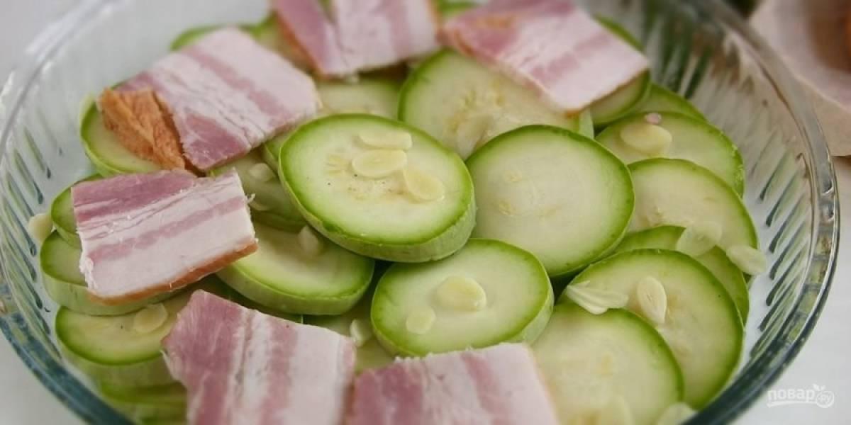 2.  Бекон также нарежьте пластинками. Форму для выпечки смажьте растительным маслом и выложите слоями ингредиенты: кабачки, нарезанный пластинками чеснок и бекон.