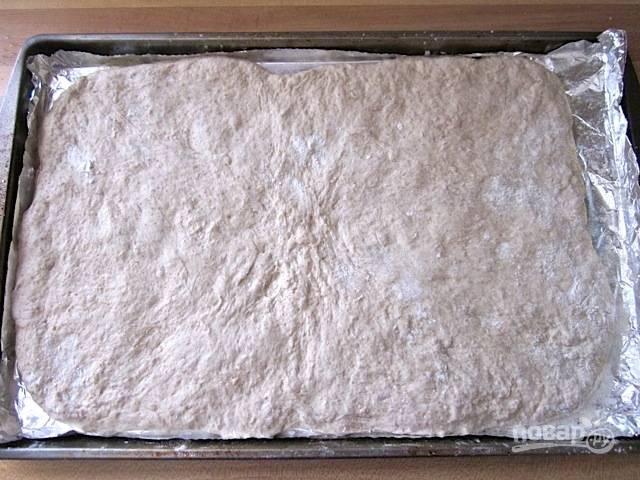 5.Посыпьте противень кукурузной мукой, затем выложите тесто и разровняйте его руками по всей поверхности.