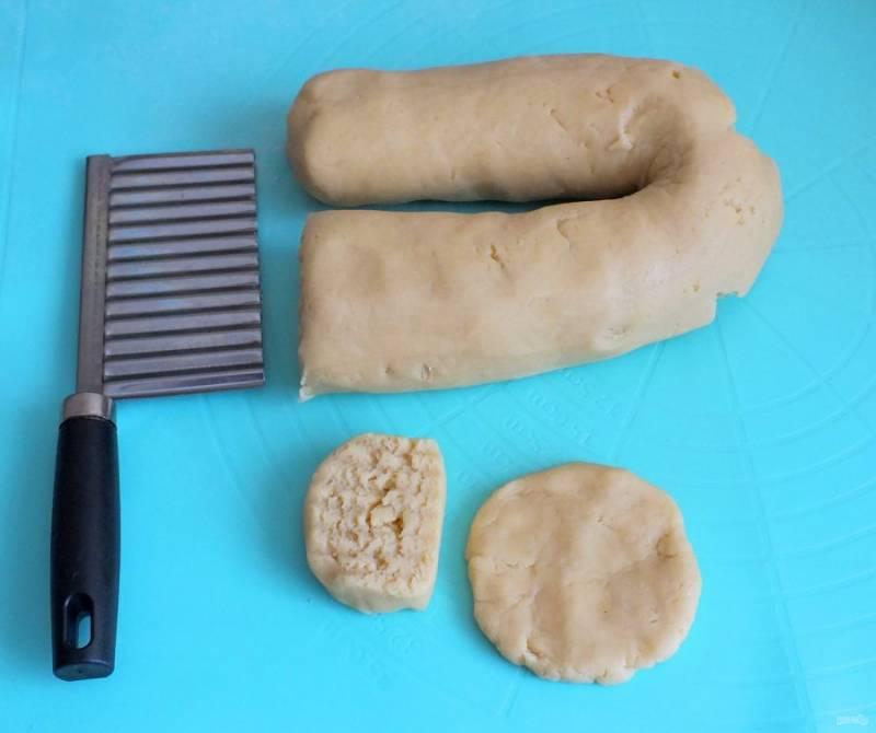 С помощью ножа нарежьте тесто на 18-20 частей. На ладони разомните кусочек в лепешечку.