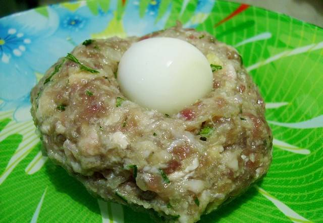 3. Из фарша лепим котлетки, внутрь помещаем яйцо. Раскатываем в руках так, чтобы яйцо нигде не выглядывало.