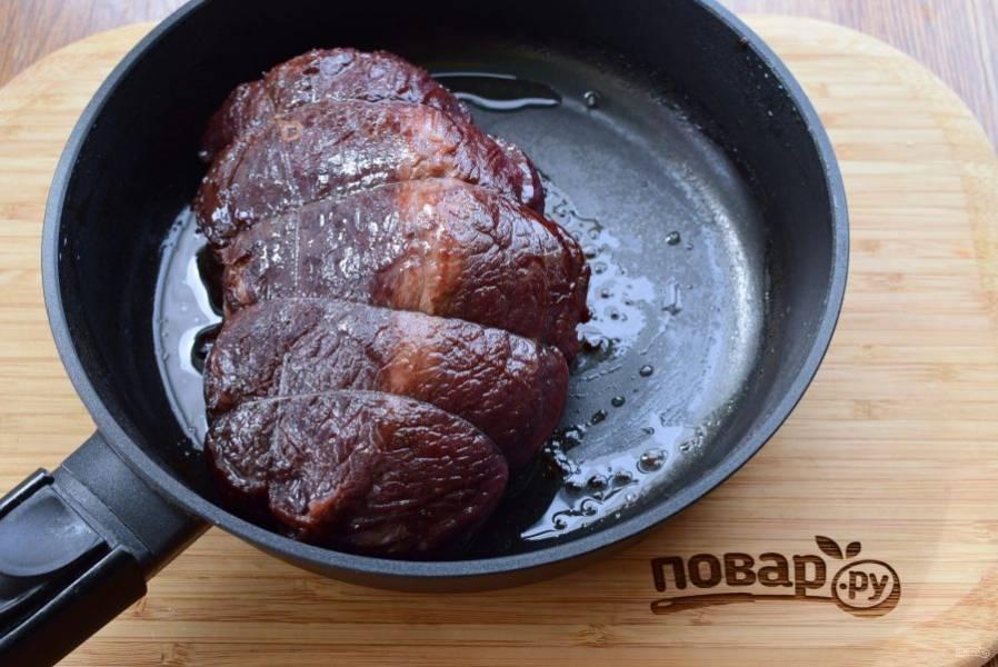Мясо тщательно обсушите, перевяжите кулинарной нитью. Маринад с мяса процедите, овощи выбросьте. Мясо обжарьте на разогретом оливковом масле со всех сторон до румяной корочки.