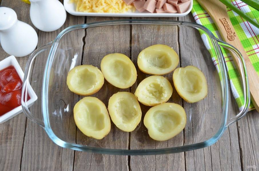 Готовый картофель разрежьте на половинки. С помощью чайной ложки удалите часть мякоти, чтобы получились лодочки.