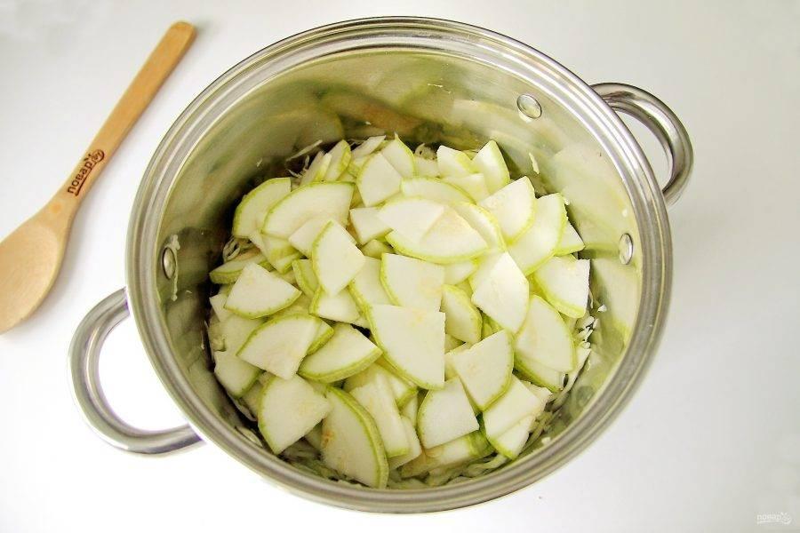 Кабачки вымойте и нарежьте кружочками. Затем каждый кружок разрежьте еще на 2-4 части. Если шкурка достаточно толстая, то ее предварительно нужно снять. Добавьте кабачки к капусте.