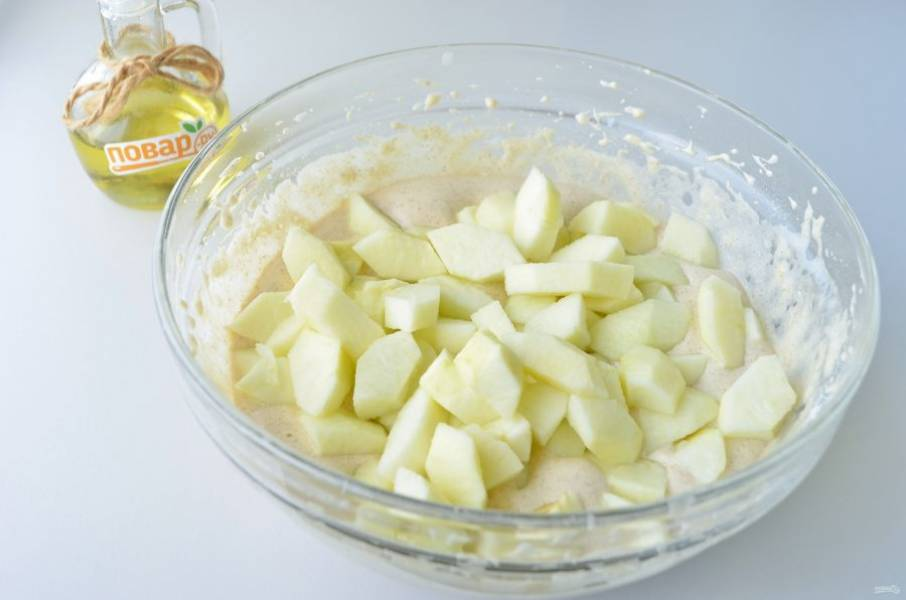 6. Яблоки очистите от кожуры, удалите сердцевинки, нарежьте кусочками и добавьте в тесто. Перемешайте.