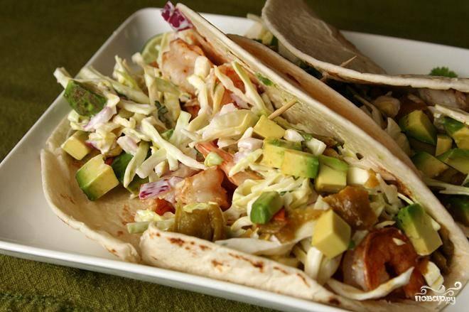 4. С помощью двух ложек разделать рыбу на маленькие кусочки. Полить оставшимся соком лайма и перемешать. Выложить на лепешки тортильяс рыбу и капустный салат, а также любую начинку по желанию.