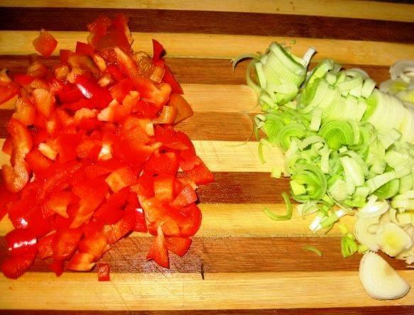 Порежьте лук-порей и сладкий перец и обжарьте их на сковороде, затем добавьте шпинат, капусту и специи по вкусу.