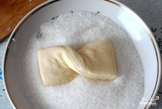 Насыпьте в пиалку сахар. Каждый бантик окуните сначала в масло, а потом — в сахар с одной стороны.