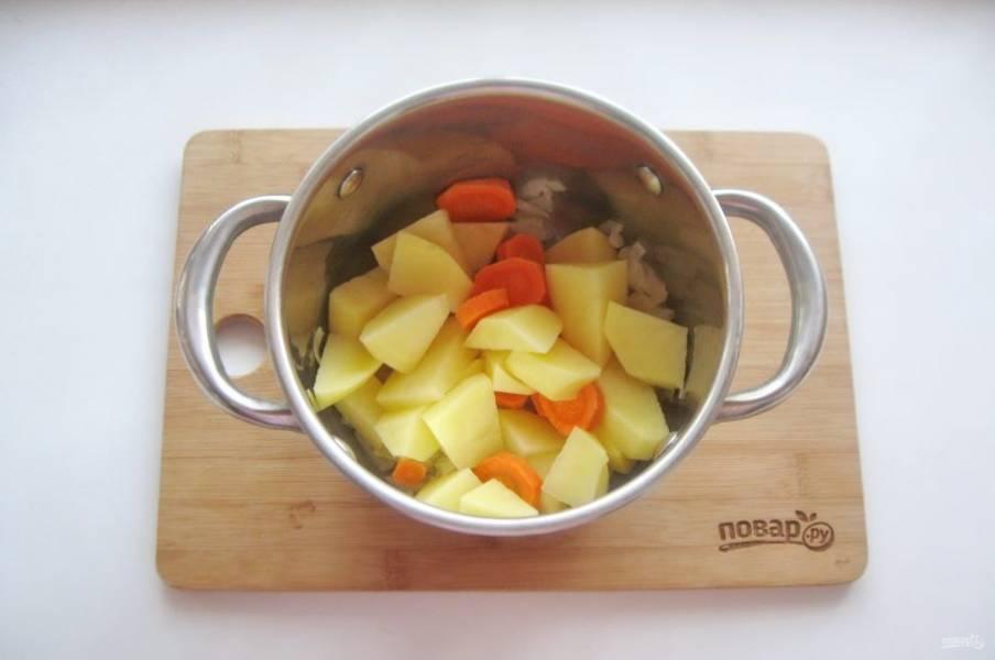 Картофель и морковь очистите, помойте, нарежьте произвольно и выложите в кастрюлю с луком.