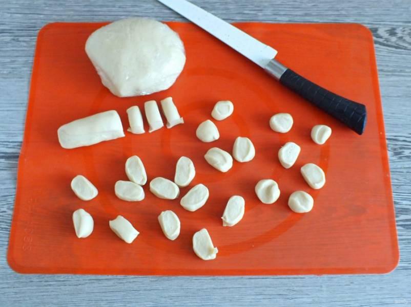 По истечении времени достаньте тесто из холодильника. Оно не требует дополнительного подпыления мукой. Отрежьте кусочек теста, раскатайте валик, нарежьте на небольшие кусочки. Каждый кусочек слегка приплюсните пальцем.