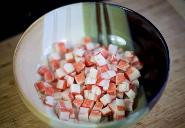 """1. При приготовленим салата """"Лакомка"""" можно использовать как отварную, так и консервированную фасоль. Во втором варианте ее нужно сварить заранее. Крабовые палочки нарезать небольшими кубиками и отправить в глубокую мисочку."""
