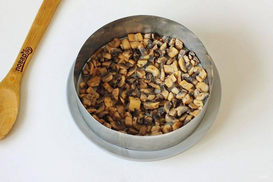 Лук и грибы нарежьте кубиками и обжарьте по отдельности на сливочном масле. Первым слоем положите обжаренные грибы. Посолите, поперчите и смажьте майонезом.